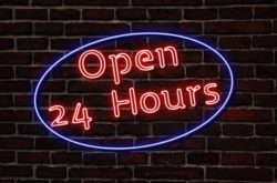 Red neon Open 24 Hours sign surrounded by purple neon circle on black brick wall
