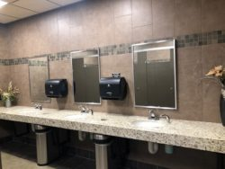 Clean public restroom with granite counter, three sinks and three mirrors.