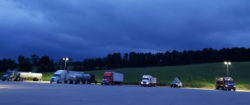 Semi trucks and trailers parked under a blue night sky