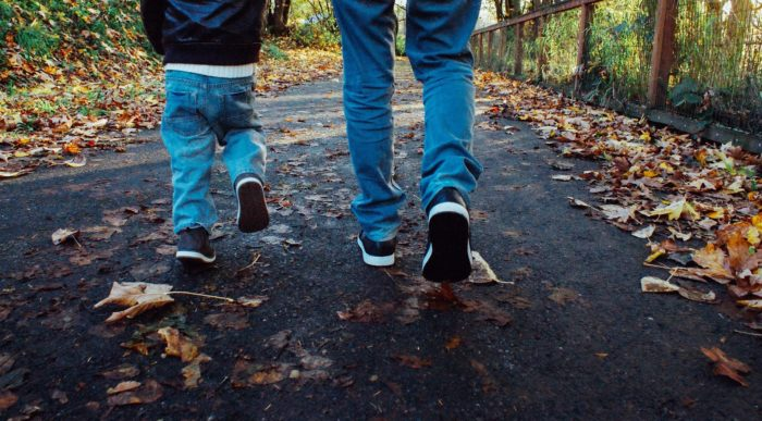 child and adult feet walking on leaf covered trail