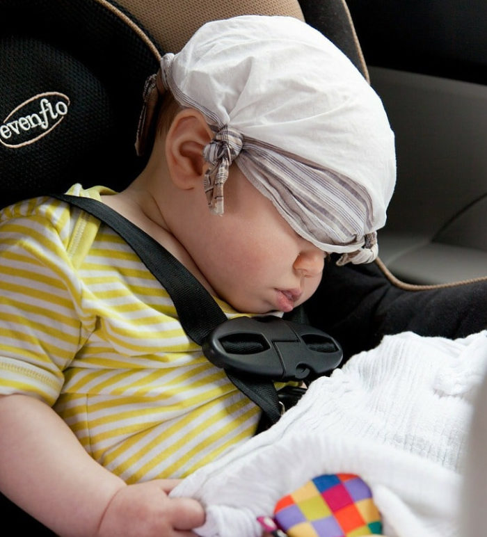 Infant wearing a yellow and white striped shirt in an Evanflo car seat slumped down sleeping while a tiny white bandanna covers his eyes.