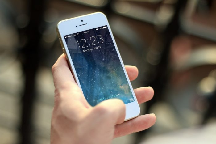 Hand holding a white iPhone with a blue starry galaxy as the lock screen cover.