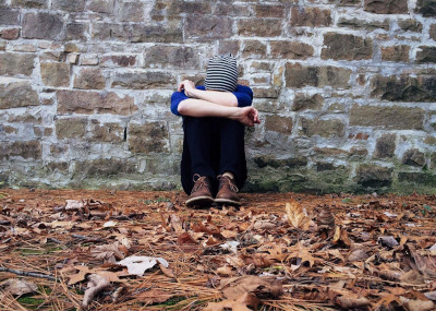 Lonely individual sitting against a brick wall with head in arms