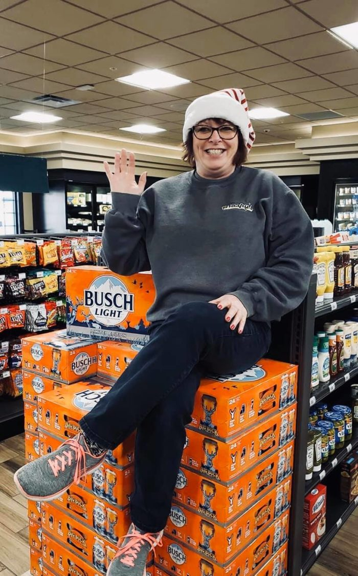 Waspy's manager sitting on cases of beer.