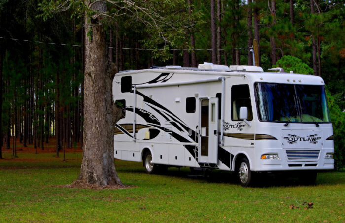 White RV parked under a tree awaiting an RV waste station