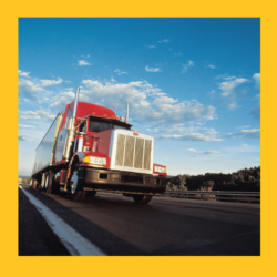 red semi-truck driving on highway with yellow border